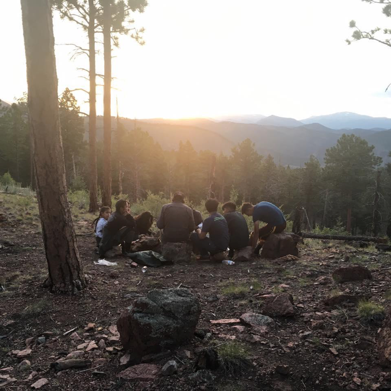 youth sitting around on rocks in the mountains. Photo: Shane Wright/Groundwork Denver