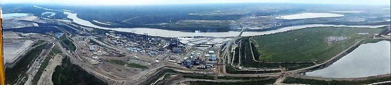 Suncor's Millenium Steepbank upgrader plant beside Athabasca river with reclaimed pond on right