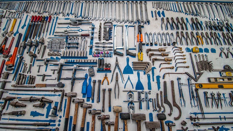Many different tools, spread out on a white canvas