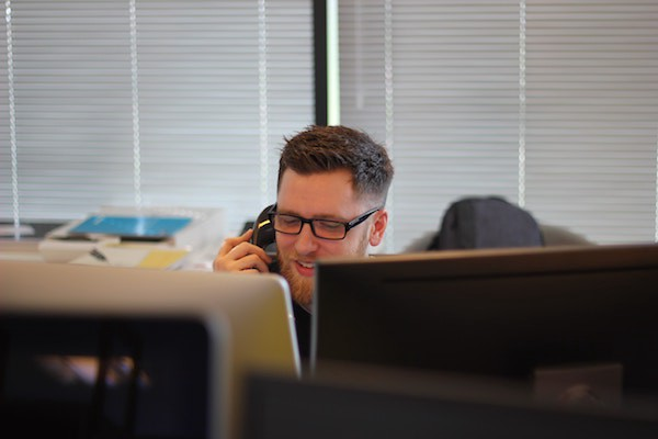 Man on a telephone talking to a client while sitting behind his computer monitor.