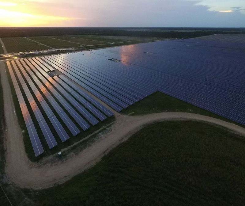 aerial view over solar field at sunset