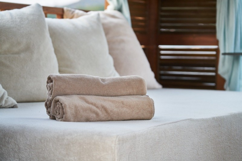 Bed with rolled towels on it