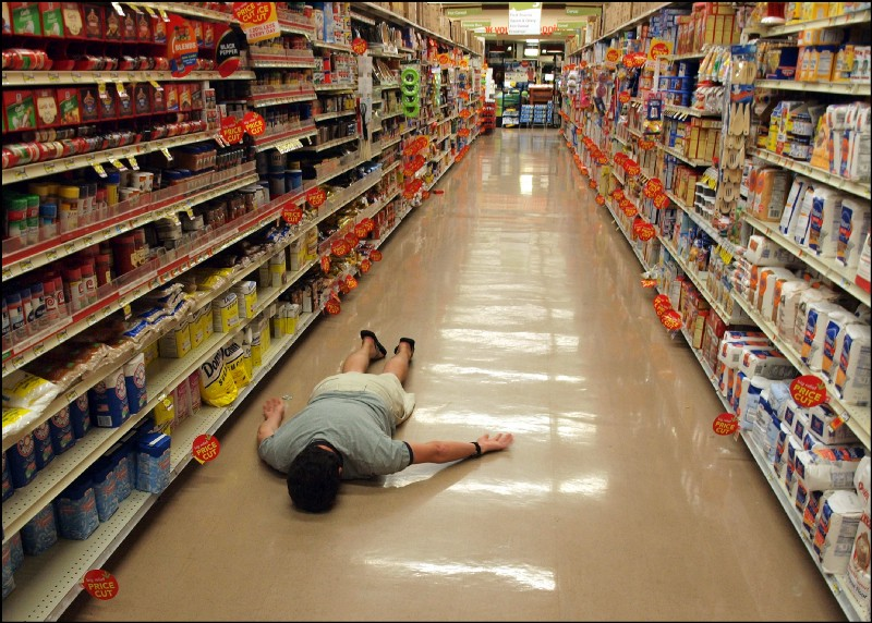 A man lying face-down on a supermarket aisle