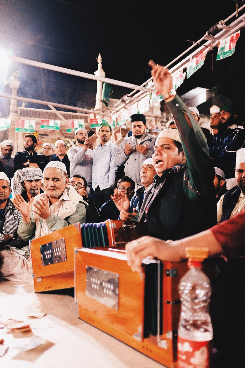 photo essay a god wherever you look kajal magazine members of the niazi nizami brothers engage in a session of qawwali as a man in the background prays to the patron saint at nizamuddin auliyah dargah in old