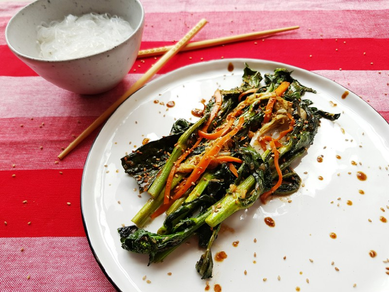 A plate with fried asian greens, next to a bowl of rice