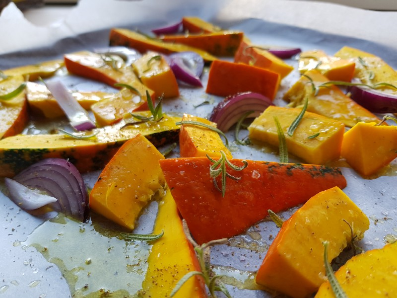 Wedges of pumpkin and red onion, covered with olive oil and rosemary