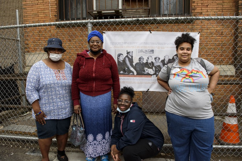 A group of women pose in front of a criminal justice system advocacy banner, hanging on a fence
