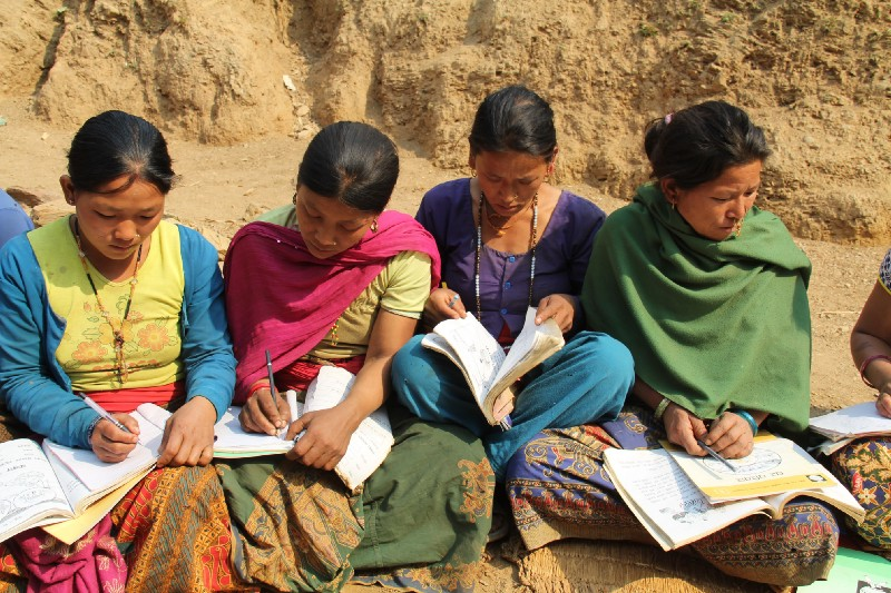 Four Nepali women sit outside in a dirt field, writing in small notebooks