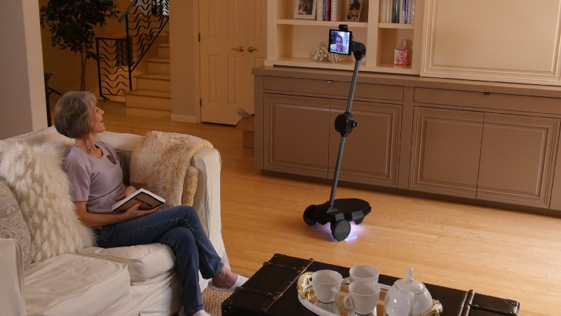 Photo of a telepresence robot in the livingroom, and an elderly woman chatting with her family on the robot.