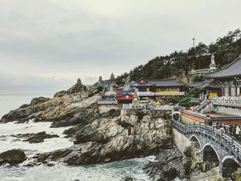 Waves against jagged rocks; with picturesque, Korean buildings above it.