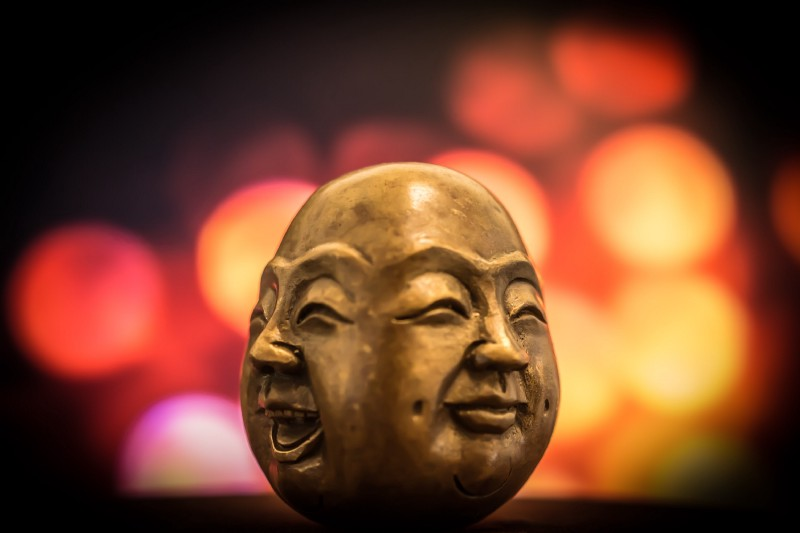 An image of a carved egg shaped sculpture with a happy and neutral face on each side.
