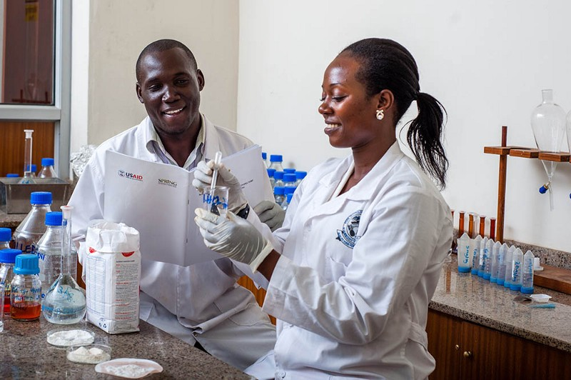 Thomas Okoth and Justine Nabuuma of the Uganda Industrial Research Institute (UIRI) perform an iron spot test to determine if maize flour marked with the fortification logo is actually fortified. / SPRING