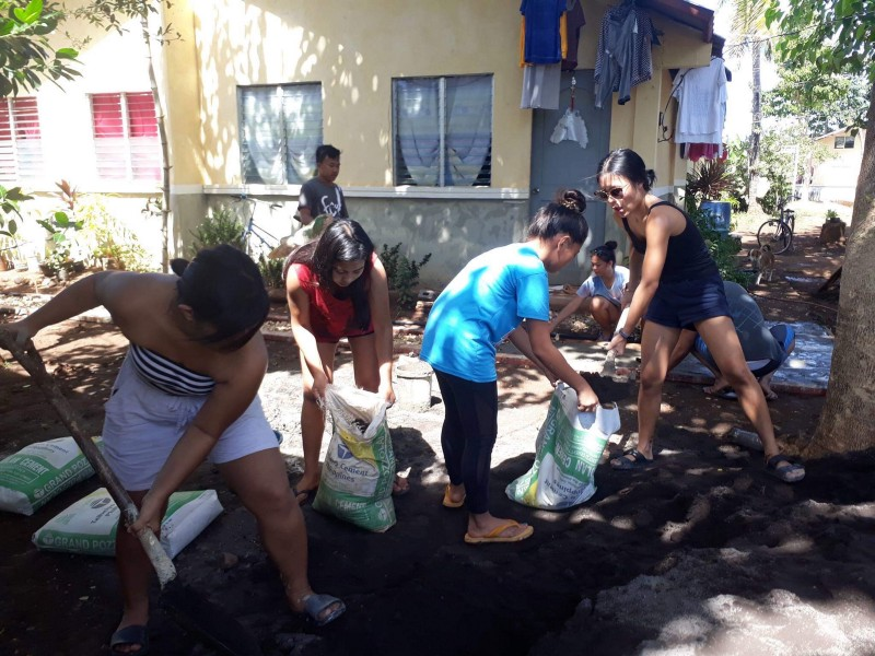 Isan and other volunteers preparing the soil that to mix with the cement