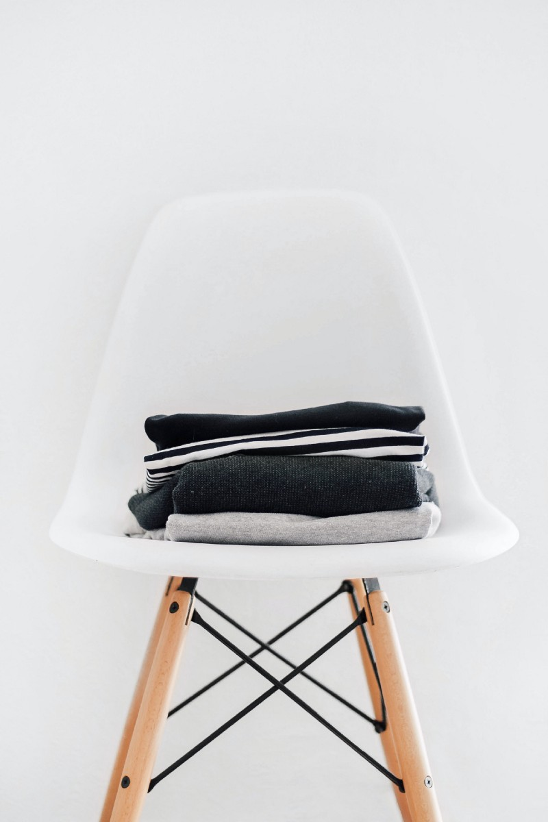 White chair with a neat pile of folded clothes.