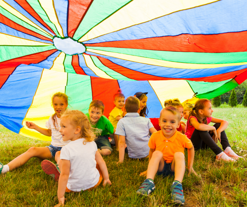 Primary school aged children sitting in a field underneath a coloured parachute.