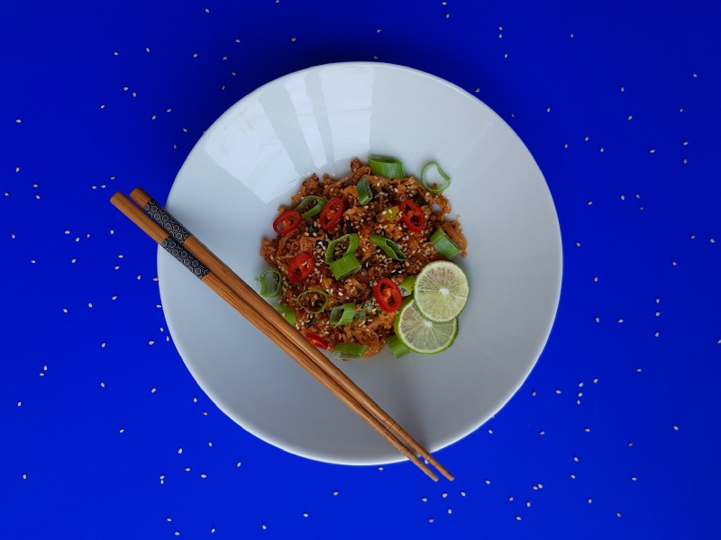 A bowl of cabbage and egg stir-fry in front of a blue background