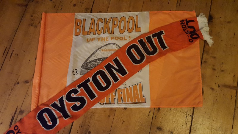 A tangerine scarf and flag. Programmes, other scarves, tops, hat and other Blackpool _paraphernalia_  are out ofshot.