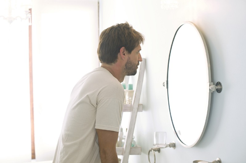 A man looks at his reflection in the mirror. He appears confused.