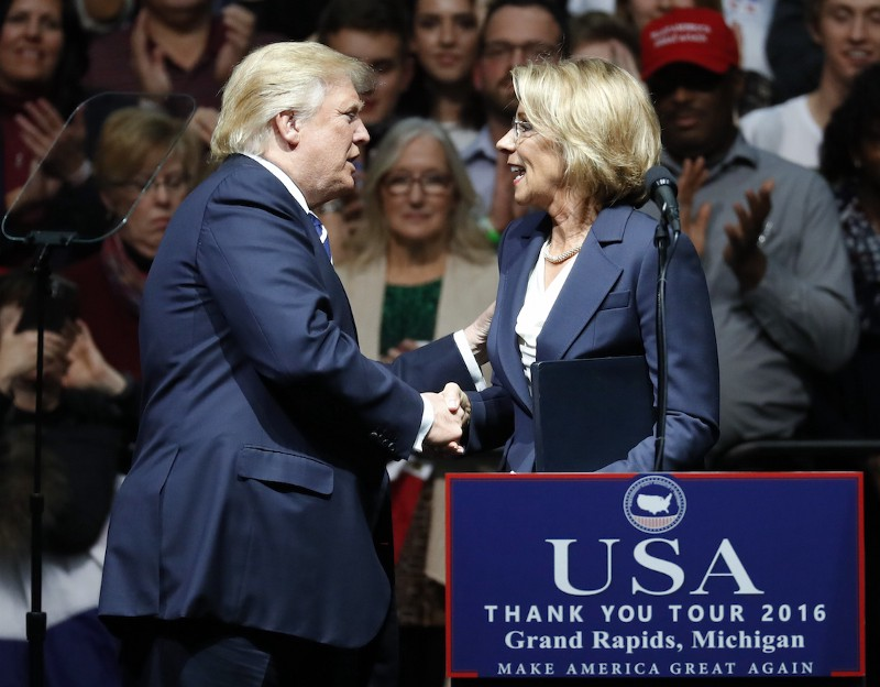 President-elect Donald Trump shakes hands with his pick for Education Secretary Betsy DeVos during a rally, in Grand Rapids, Mich., Friday, Dec. 9, 2016 CREDIT: Paul Sancya