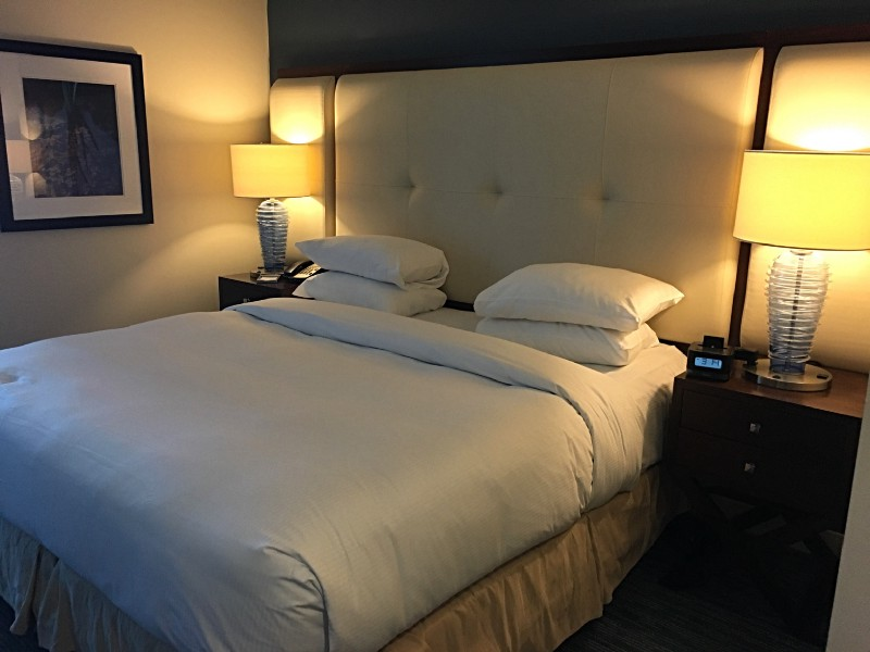 King sized bed, pillows, headboard, nightstands, blue lamps, picture frame on wall