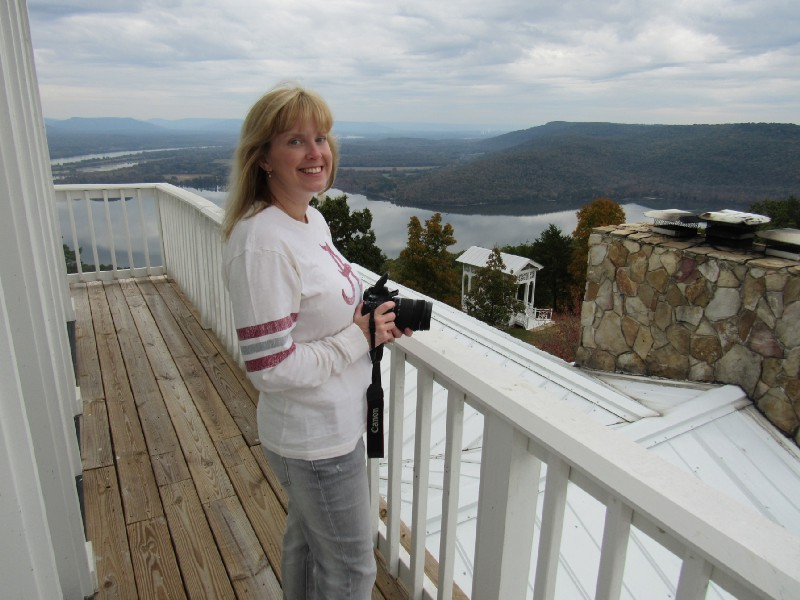 Meredith Cummings with her camera, on a balcony.