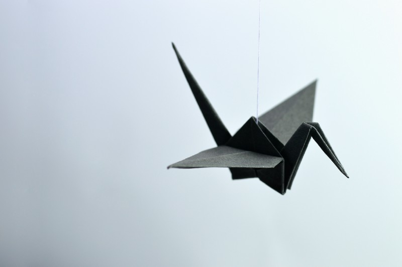 Paper Black Origami Crane Bird hanging on a string attached to the ceiling