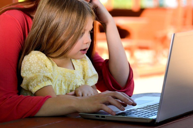 Picture of young girl and adult typing on a computer