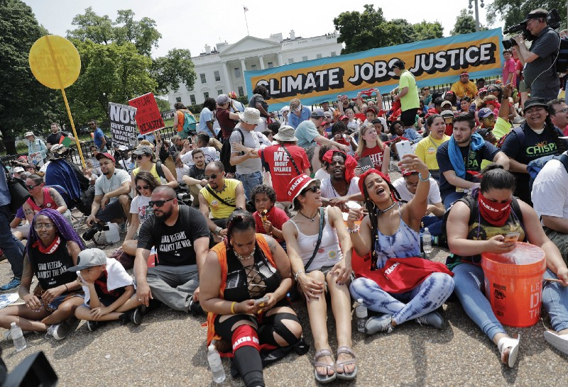 Demonstrators sit on the ground along Pennsylvania Ave. in front of the White House in Washington, Saturday, April 29, 2017, during a demonstration and march. CREDIT: AP Photo/Pablo Martinez Monsivais