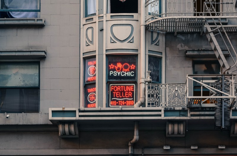 A shot of a building window with Psychic and Fortune Teller written on neon signs.