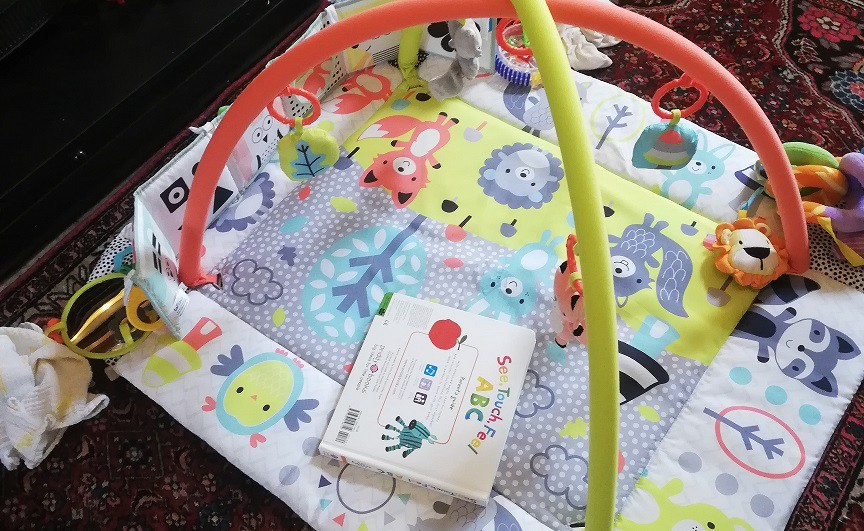 A baby's play mat, covered in colourful animal pictures, toys and an ABC book