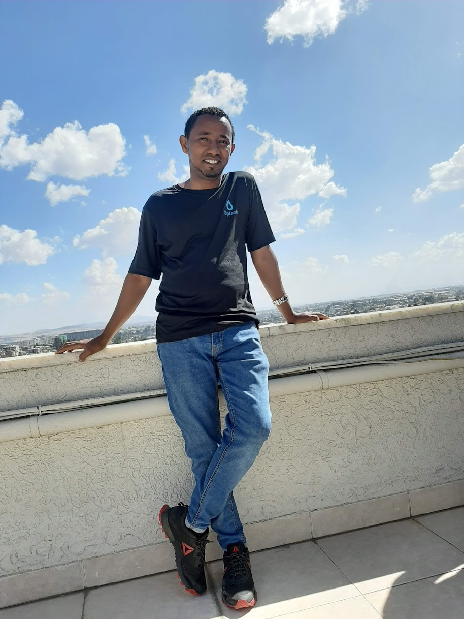 Splash staffer Nasser Ferej stands smiling on a rooftop in a black shirt and jeans, with a beautiful blue sky and picturesque clouds in the background.