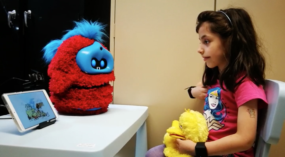 Girl speaking to social agent robot that is hooked up to tablet application.