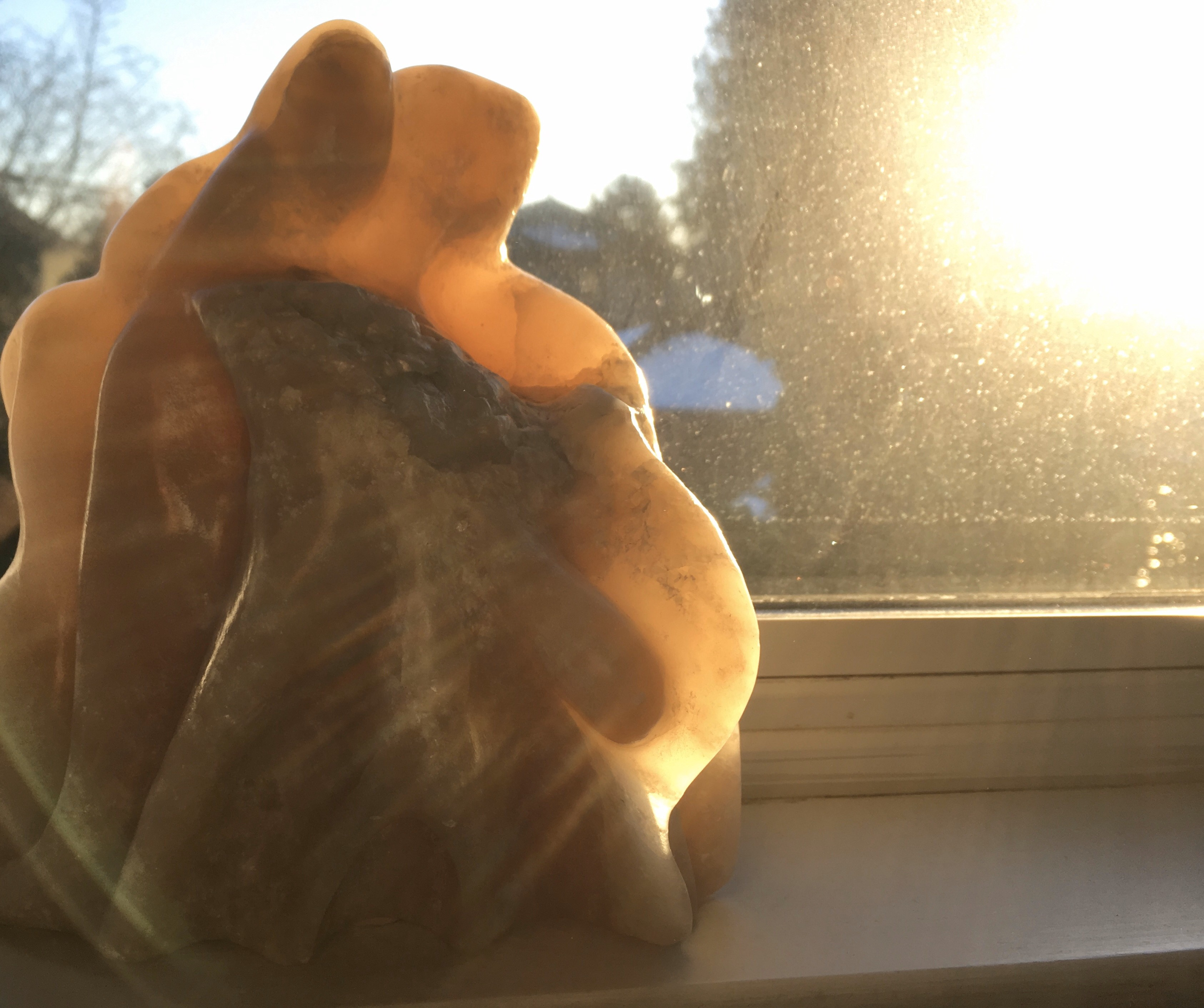 Winter sun shines around and through warm beige alabaster carved with 2 figures looking down together holding a child