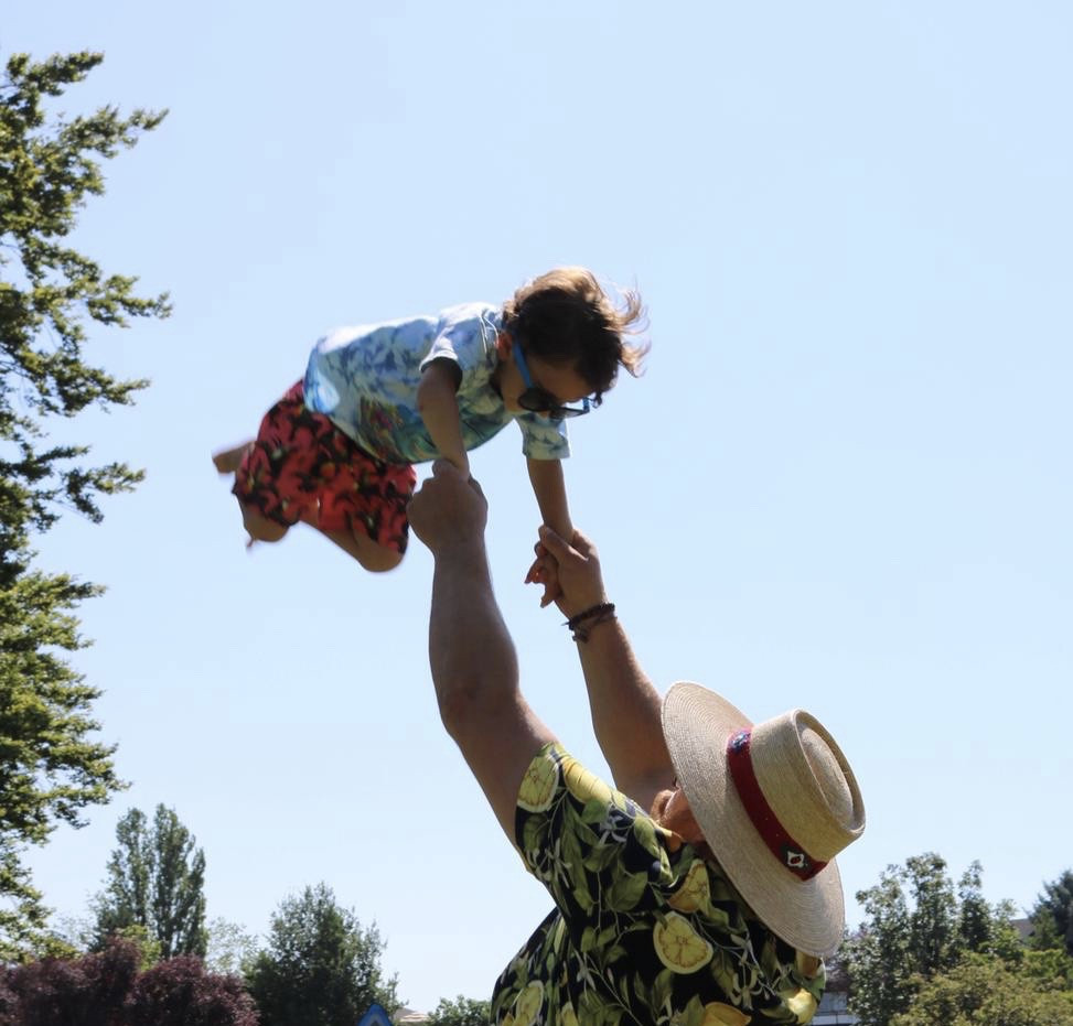 A 3 year old boy with dangling sunglasses is suspended high above his uncle holding him up with outstretched arms.