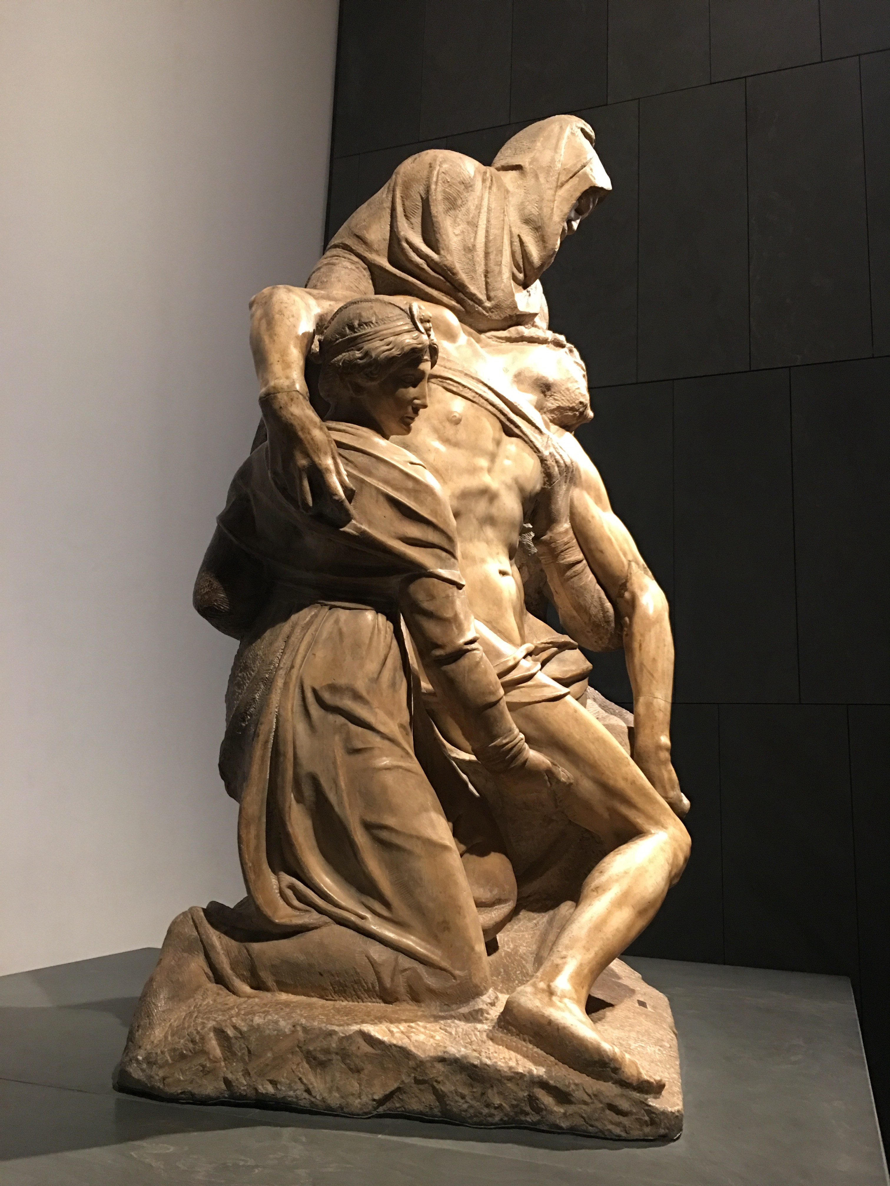 3 figures in marble; Mother Mary, Mary Magdalene and Joseph of Arimathea support Christ's limp body.